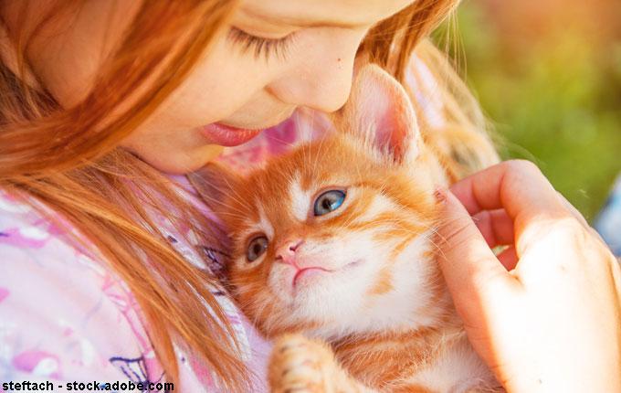 Mädchen kuschelt mit Kitten