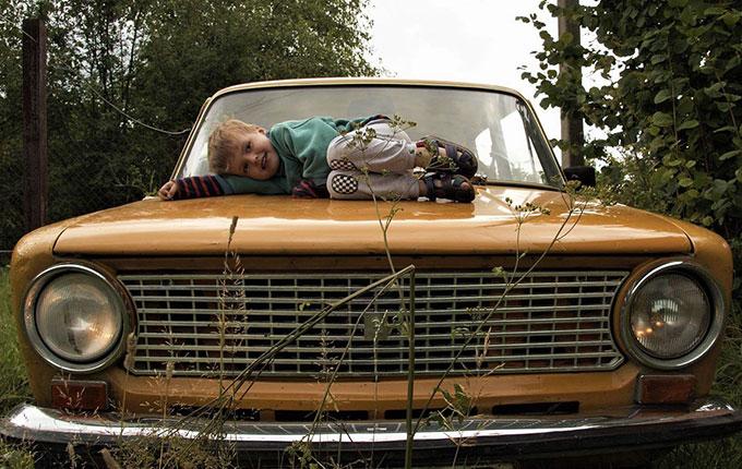 Kind liegt grinsend auf Motorhaube vom Auto
