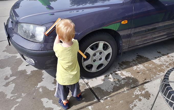 Kind säubert Auto mit Windschutzscheibenabzieher