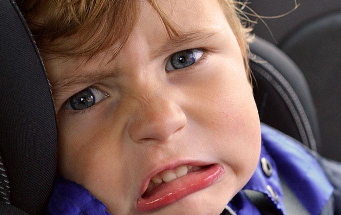 Kind sitzt im Autositz und guckt grimmig