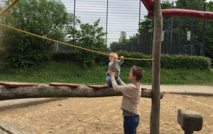 Spielplatz - Mutter hält Kind beim Balancieren
