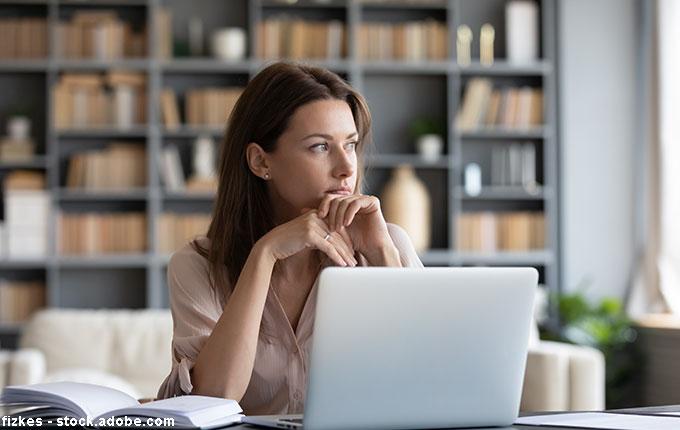 nachenkliche Frau abgelenkt von der Arbeit am Laptop
