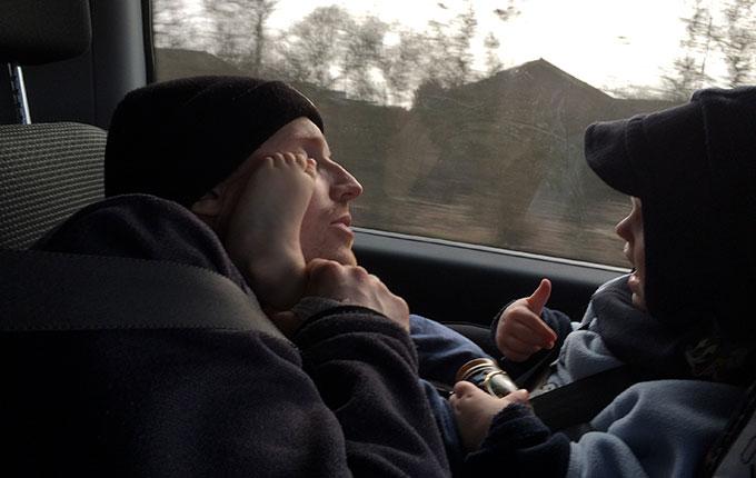 Papa spielt mit Kind während der Autofahrt