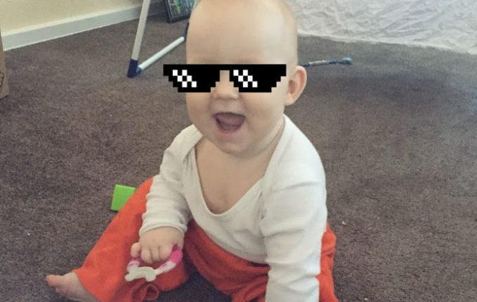 Baby sitzt, lacht und hält Beißring in der Hand