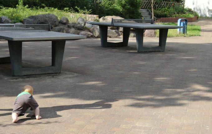 Spielplatz in der Forster Straße - Kind krabbelt Richtung Tischtennisplatten