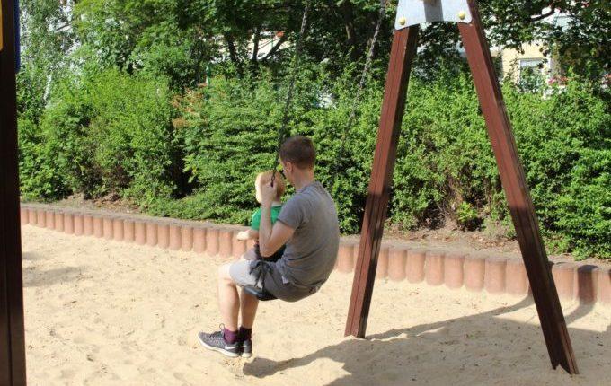 Spielplatz in der Forster Straße - Vater schaukelt mit Sohn