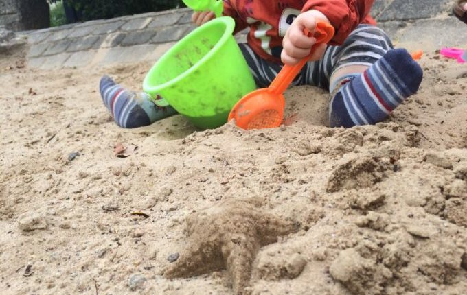 Spielplatz in der Louis-Lewin-Straße - Kind spielt im Sand mit Buddelzeug