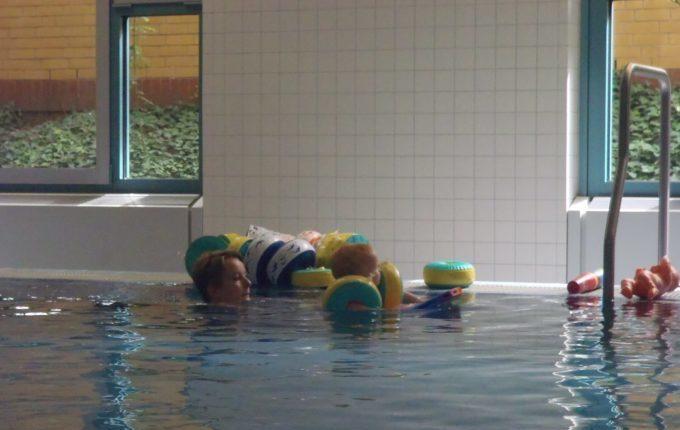 Babyschwimmen - 10. Tag - Mutter schwimmt mit Kind auf Schwimmbrett durchs Wasser