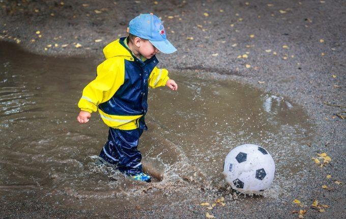 Die passende Bekleidung für mein Baby - Junge spielt mit Fußball im Regen