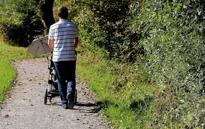 Sommertipps für Familien mit Baby und Kind - Mann fährt Kinderwagen mit Sonnenschirm