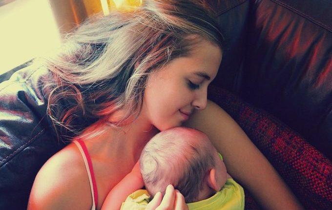 Warum weint mein Baby - Mädchen kuschelt mit Baby