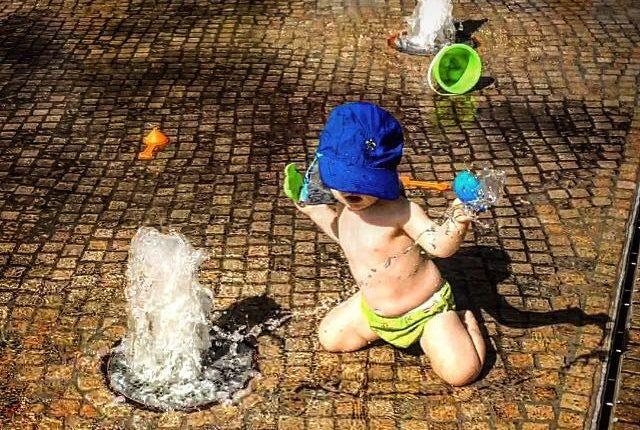 Springbrunnenplatz - Kind spielt am Springbrunnen