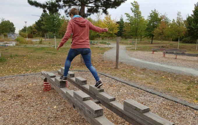 Der Buchstaben- und Balancierspielplatz in der Sebnitzer Straße - Frau balanciert breitbeinig