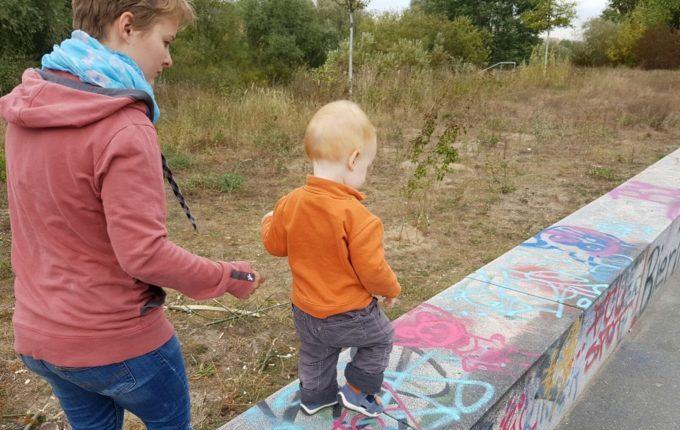 Der Buchstaben- und Balancierspielplatz in der Sebnitzer Straße - Kind läuft auf Steinbank