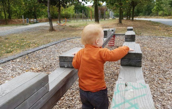Der Buchstaben- und Balancierspielplatz in der Sebnitzer Straße - Kind läuft zwischen Balken