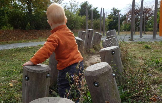 Der Buchstaben- und Balancierspielplatz in der Sebnitzer Straße - Kind zwischen Baumstämmen