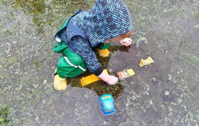 Kind spielt mit Autos in großer Regenpfütze