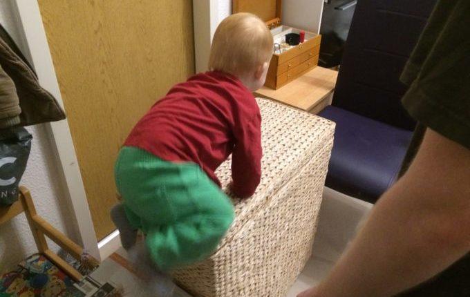 Wenn der Abend länger wird... - Kind klettert über Wäschekorb