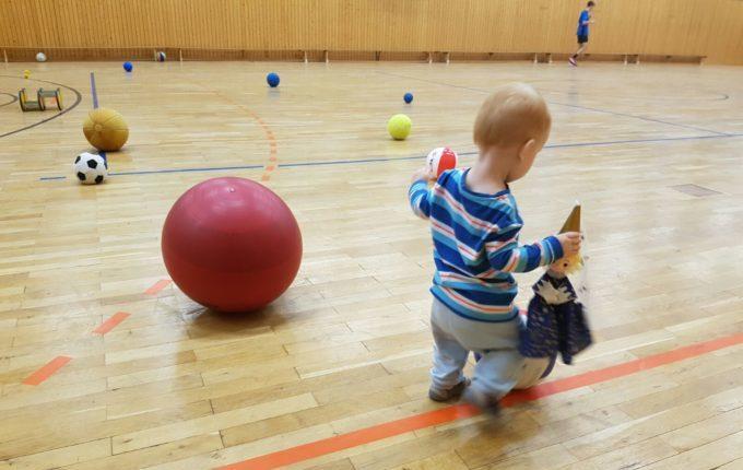 Dienstag geht's in die Turnhalle - Kind spielt mit Bällen