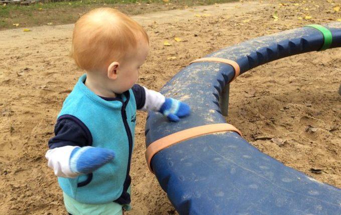 Spielplatz in der Suhler Straße - Kind säubert Karussell