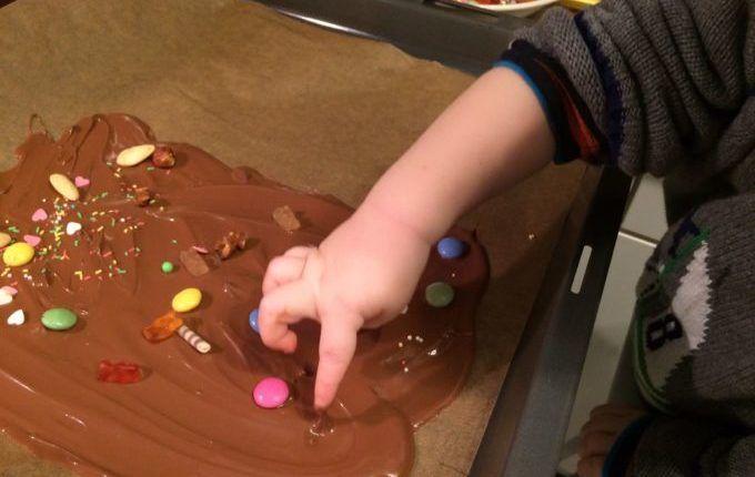 Bruchschokolade - Kind taucht Finger in geschmolzene Schokolade