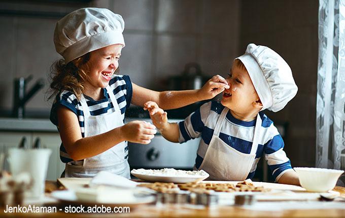 Kinder albern beim Backen herum und lachen