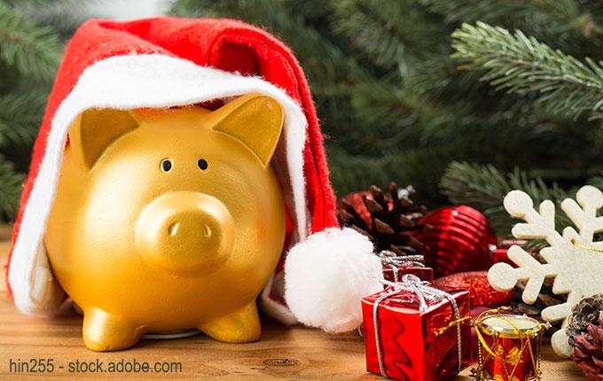 Sparschwein mit Weihnachtsmütze und Geschenken