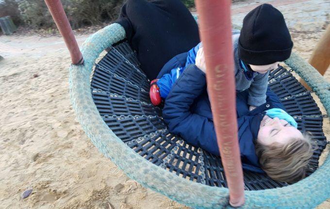 Spielplatz in der Albrecht-Dürer-Straße - Frau schaukelt mit Kind