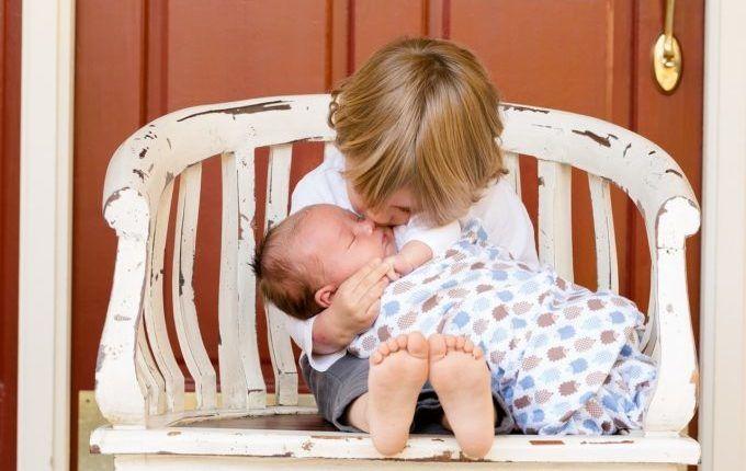 Kind küsst Baby