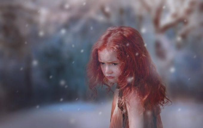 Kind mit roten Haaren kurzärmelig im Schnee