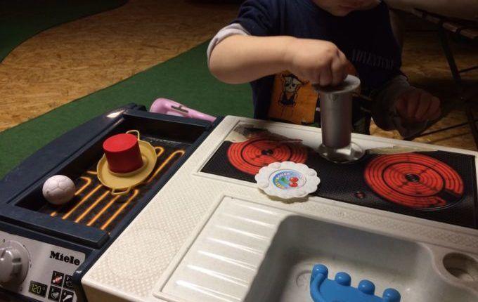 Kindercafé Driss im Wunderland -Kind spielt mit Küche