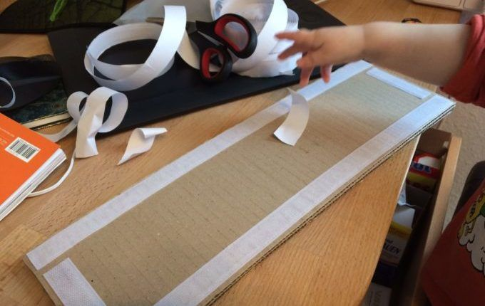 Meine To-do-Liste als Mutter - Kind zieht Papier vom Klettband ab