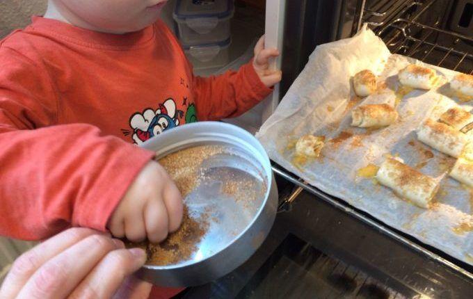 Zimtschnecken - Kind verteilt Zimt und Zucker auf den Zimtschnecken