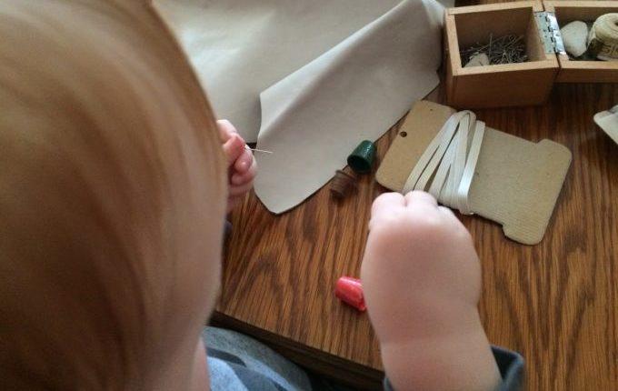 Das Indianerkostüm vom kleinen Mann - Kind spielt mit Nadel und Fingerhut