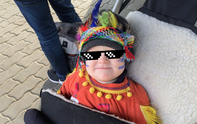 Kind in Indianerkostüm mit Kopfschmuck und Schminke