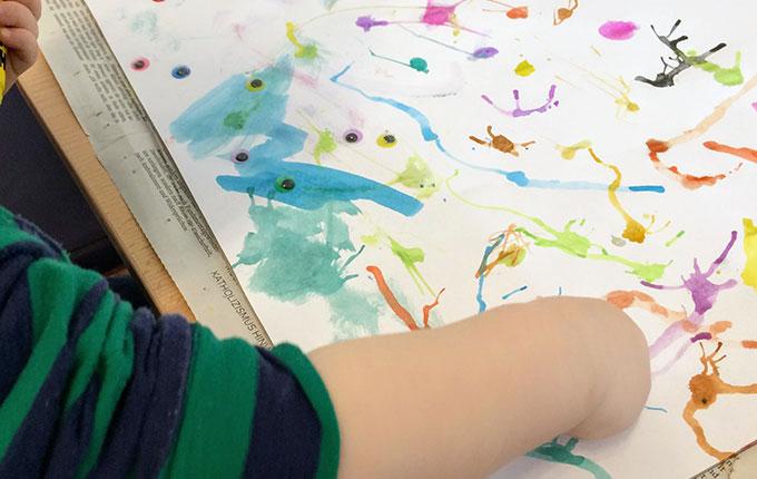 Kind klebt Wackelaugen auf Wasserfarbenmonster
