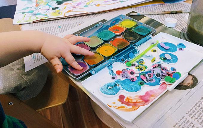 Kind malt mit Finger im Tuschkasten herum