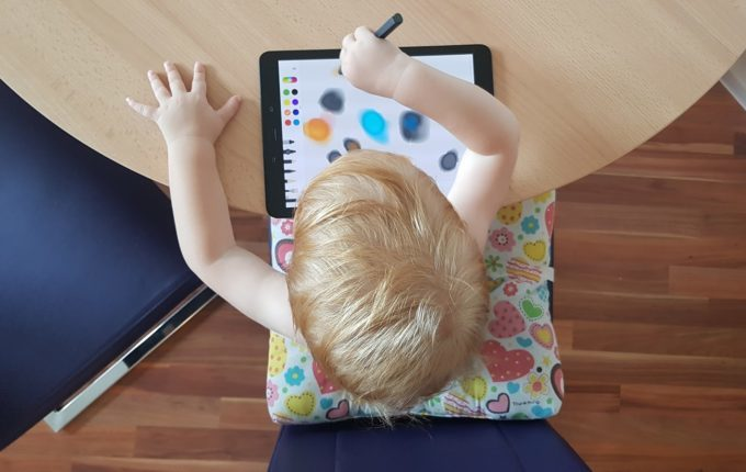 Kind malt mit Stift auf Tablet