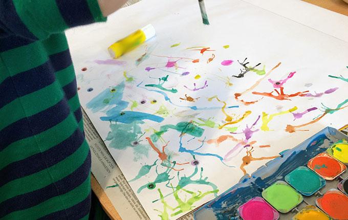 Kind malt mit vollem Elan mit Pinsel auf Papier