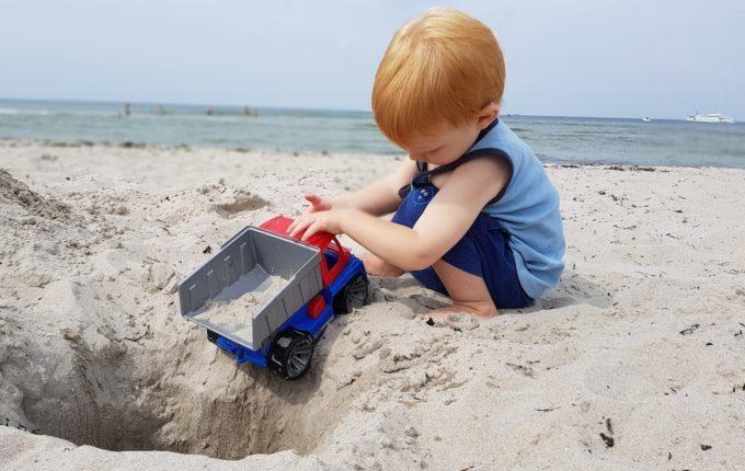 Kind spielt am Strand mit Kipplaster