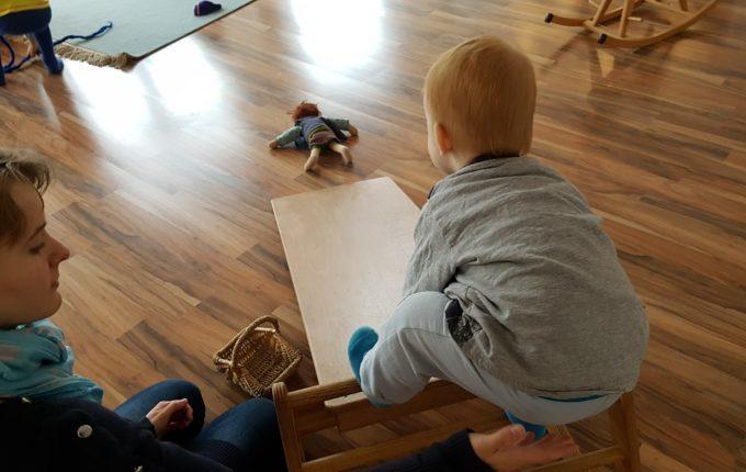 Kindercafé Sonnenkind - Kind rutscht mit Puppe