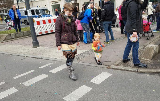 Mit Kind zum Faschingsumzug - Mutter und Kind laufen mit