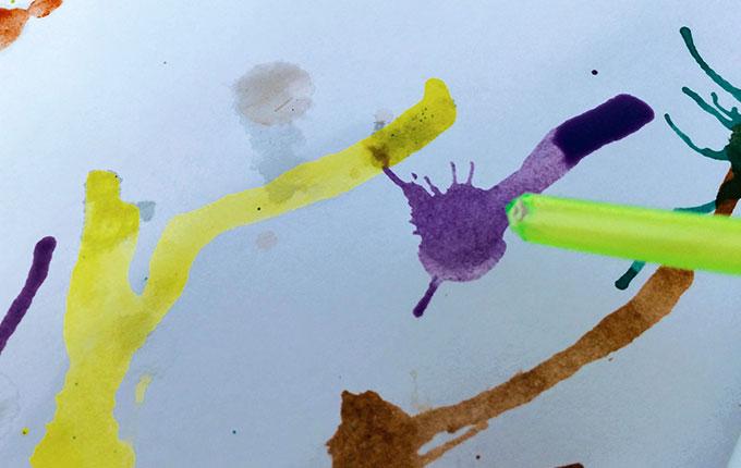 Strohhalm pustet Wasserfarbe in verschiedene Richtungen