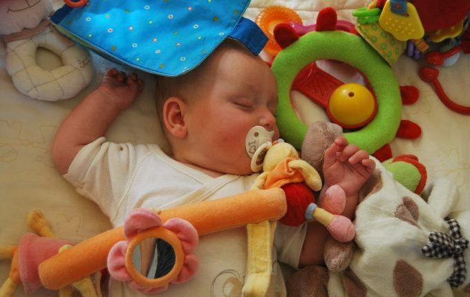 6 Tipps für eine lange, aber entspannte Autofahrt mit Kleinkind - Baby umgeben von Spielzeugen