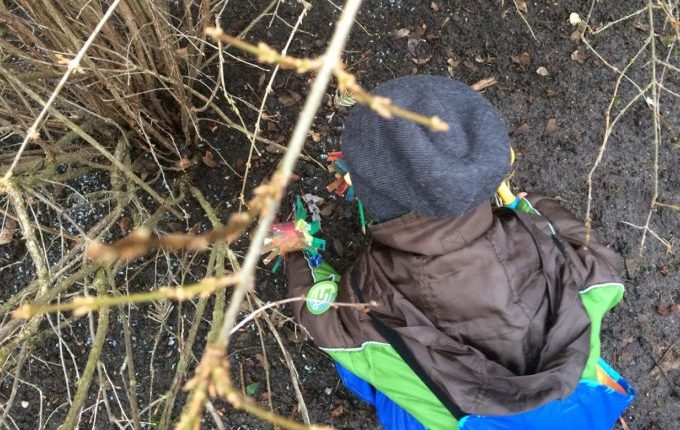 Frühlingsblumen - Kind steckt Frühlingsblumen in die Erde