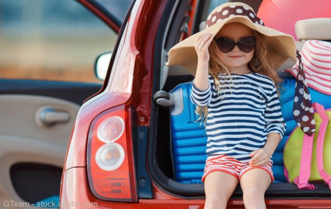 Kind sitzt mit Sonnenhut im Kofferraum