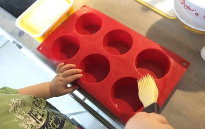 Toast Muffin mit Ei - Kind fettet Muffinform mit Pinsel ein