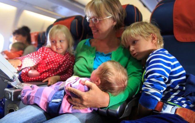 Fliegen mit Kindern - Frau mit drei Kindern im Flugzeug
