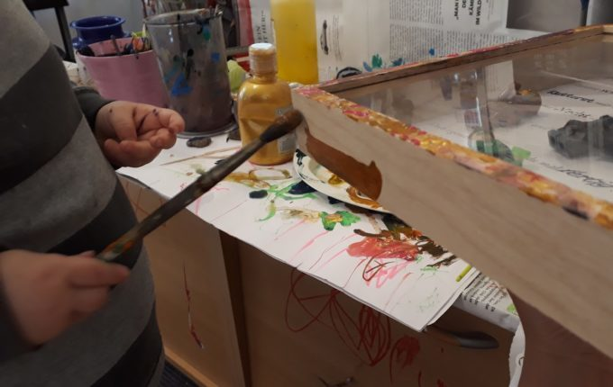 Geschenk für Superhelden - Kind bemalt mit Pinsel und Acrylfarben den 3D-Rahmen