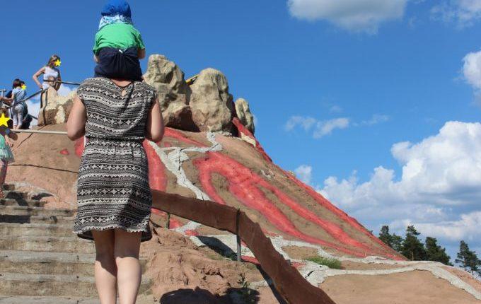 Dinopark Germendorf - Frau trägt Kind auf Schultern zum Vulkan